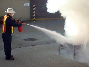 Работник использует огнетушитель на очаге возгорания